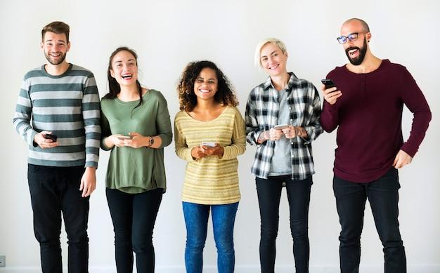 Разнообразные люди, стоящие с мобильными телефонами в руках