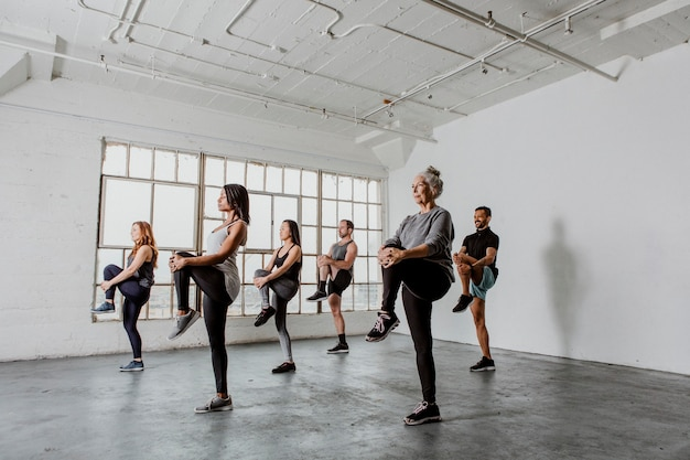 Diverse people stretching their knees in a yoga class