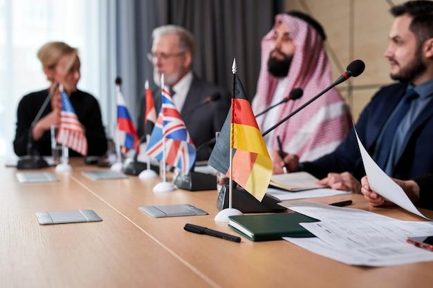 Разнообразные политические лидеры сидят с микрофонами на пресс-конференции, разговаривают, проводят собрания без галстуков, чтобы обсудить идеи и вопросы повестки дня. в современном зале заседаний. сосредоточиться на маленьком флаге