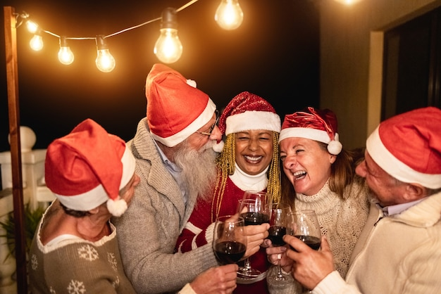 Diverse senior people having fun cheering with wine during christmas eve wearing santa clause hats - soft focus on center man face