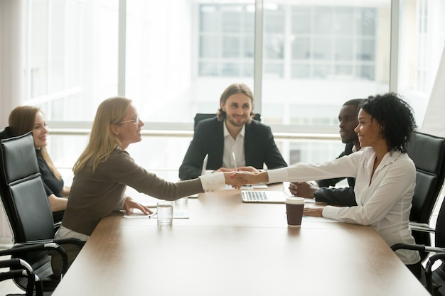 Diverse smiling businesswomen shaking hands greeting at multiracial group meeting