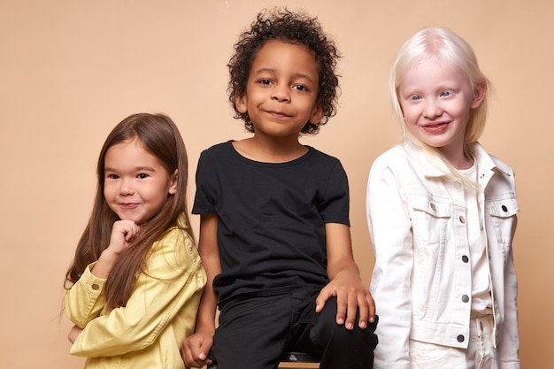 Diverse smiling positive children posing happy together