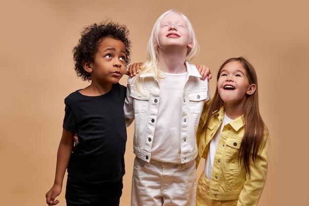 Diverse smiling positive children posing happy together