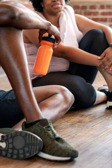Разнообразные спортивные люди отдыхают после тяжелой тренировки
