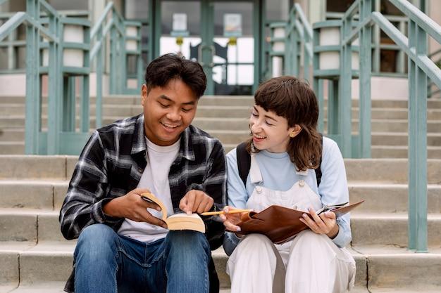 Разнообразные студенты вместе учатся в кампусе колледжа