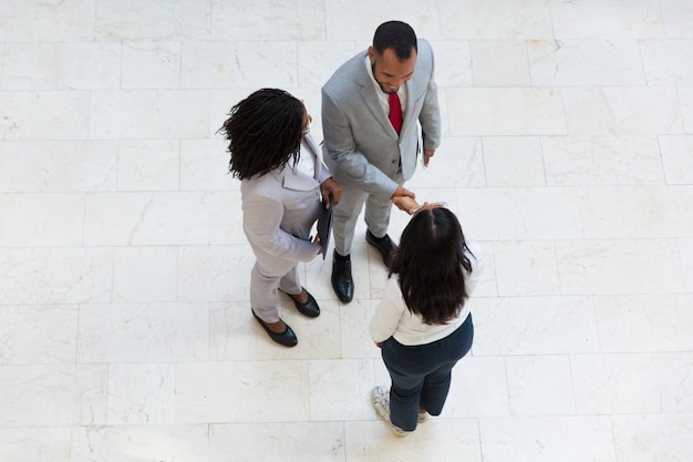 Diverse successful partners greeting each other