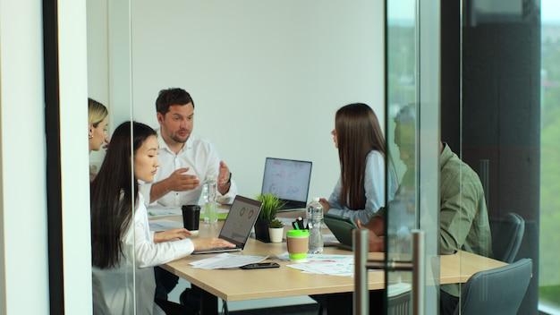 トレンディなレンガのオフィススペースのチームワークに関与する多様なチーム多民族のビジネスチーム会議ブレーンストーミング新しいアイデアを共有する