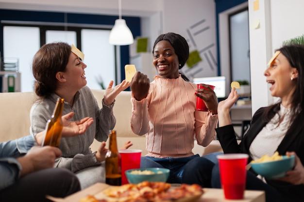 同僚の多様なチームが、ソファに座ってオフィスで仕事をした後、推測するゲームをします。楽しい陽気な活動娯楽の楽しみのためになりすましをしているアフリカ系アメリカ人の女性