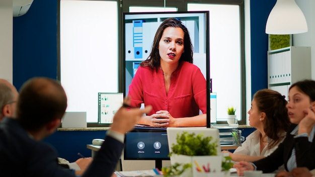 ブロードルームに座っているビジネス会議中にwebカメラを使用してプロジェクトマネージャーと話している同僚の多様なチーム。バーチャルミーティング、オンラインブリーフィングでマネージャーとやり取りする従業員。
