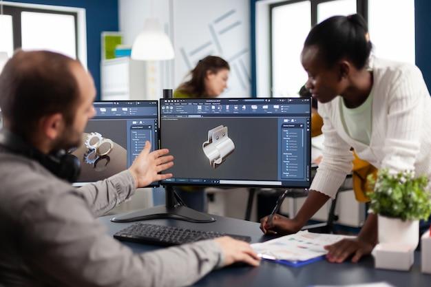 건설 금속 구성 요소를 개발하는 최신 cad 프로그램에서 작업하는 다양한 엔지니어 건축가 팀. 기어가있는 디지털 소프트웨어를 보여주는 pc에서 프로토 타입 아이디어를 연구하는 산업 디자이너