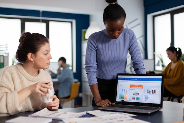 Разнообразная команда финансовой компании работает вместе над корпоративными графиками и статистикой. многонациональные сотрудники собрались в коворкинге стартапа нового бизнеса.