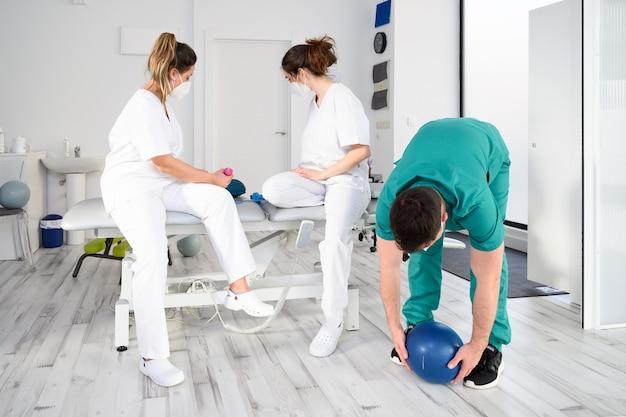 코로나 바이러스 전염병 동안 신체 재활 클리닉에서 일하는 보호용 안면 마스크를 착용하는 다양한 의료 전문가 팀