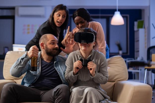 さまざまな人々のチームが、仕事の後のオフィスパーティーのお祝いでテレビコンソールでvrメガネを使用しています。多民族の同僚は、楽しいエンターテインメントを楽しんでいるジョイスティックコントローラーで遊ぶ
