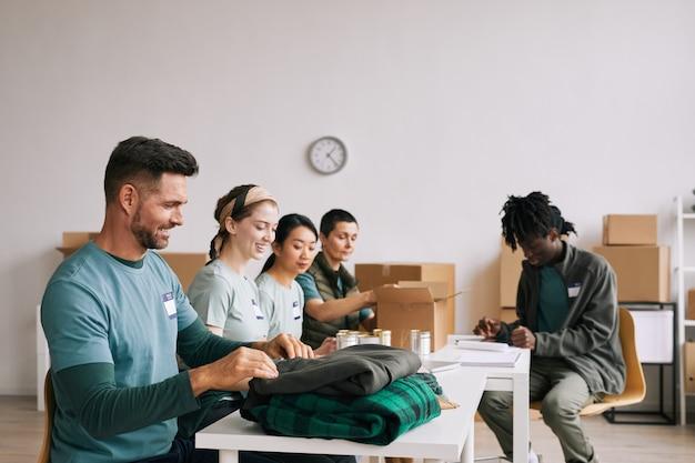 Разнообразная команда улыбающихся волонтеров, занимающихся организацией еды и одежды во время акции помощи и пожертвований
