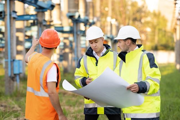 エンジニア投資家との建設現場の不動産建設プロジェクトの専門家の多様なチーム