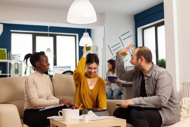 スタートアップオフィスルームのソファに座って成功を祝うハイタッチを共有する成功した若い起業家の多様なチーム