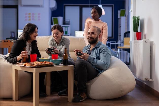 사무실에서 tv로 콘솔 게임을 하는 다양한 직원 팀