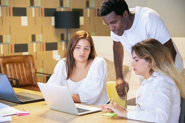 Разнообразная команда вместе смотрит презентацию на компьютере