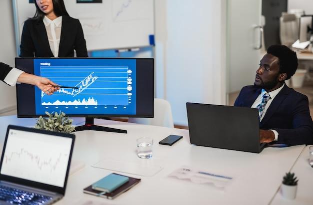 Разнообразная команда трейдеров делает анализ фондового рынка в офисе хедж-фонда - в центре внимания лицо афроамериканского мужчины
