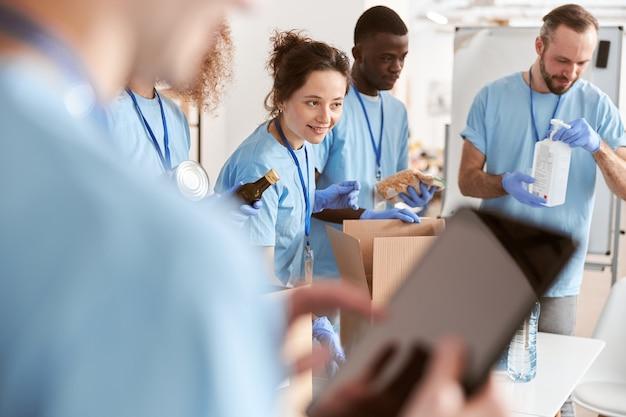 파란색 유니폼을 입은 다양한 자원 봉사자들이 함께 작업하는 판지 상자에 식료품을 분류합니다.