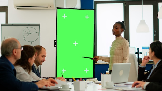 Diverse woman standing in start up office discussing strategy with green screen monitor in front of business partners. manager explaining to multiethnic team project chroma key display mock up desktop