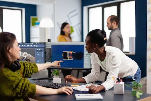 Diverse women game software developers creating game interface sitting in startup creative agency company pointing at pc displays