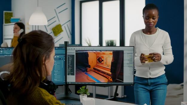 Разнообразные женские разработчики программного обеспечения для игр тестируют новую игру, сидя в стартапе, креативном агентстве, сша ...
