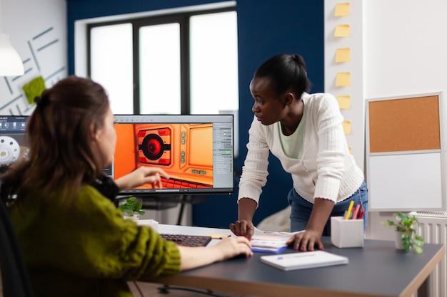 Разнообразные женские разработчики программного обеспечения для игр тестируют новую игру, сидя в стартапе креативного агентства, используя компьютер с двумя мониторами.