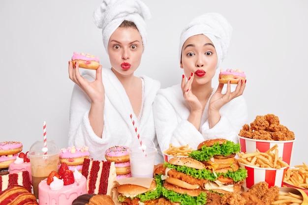 다양한 여성들이 집에서 미용 절차를 마친 후 건강한 피부를 가지고 있으며 맛있는 스낵 설탕 디저트로 둘러싸인 맛있는 글레이즈드 도넛을 들고 있습니다