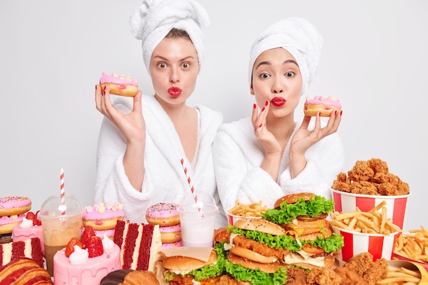 Diverse women have healthy skin after beauty procedures at home hold delicious glazed doughnuts surrounded by delicious snack sugary desserts