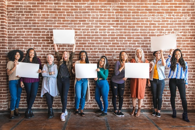 Diverse women holding a blank placard