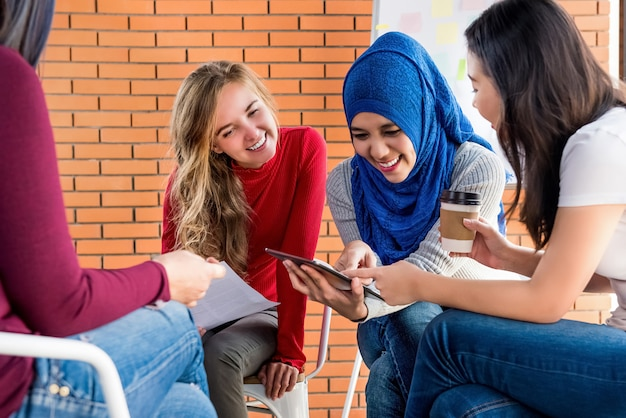 Diverse women looking at tablet pc together in group meeting