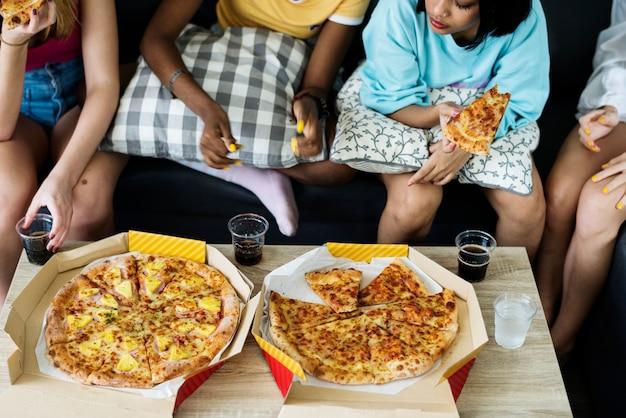 Разнообразные женщины, сидящие на диване, едят пиццу вместе