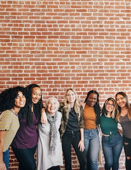벽돌 벽 옆에 함께 서 있는 다양한 여성