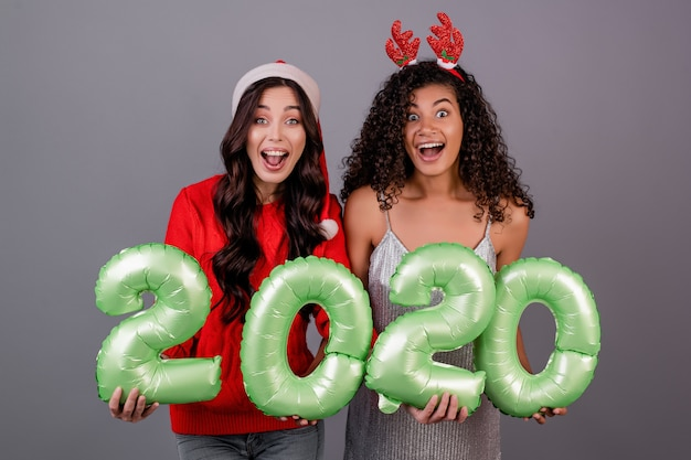 Diverse women with 2020 new year balloons wearing christmas hat isolated over grey