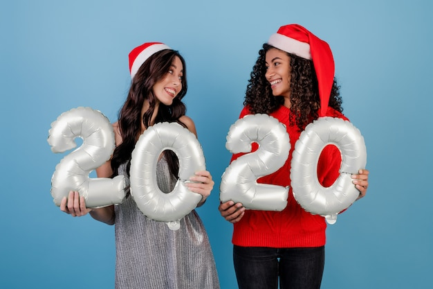 Diverse women with 2020 new year balloons wearing christmas hats isolated