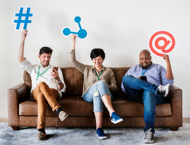 Diverse workers sitting on couch holding