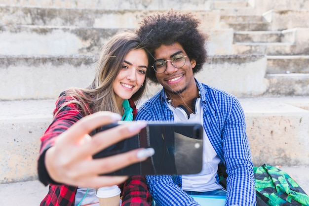 Diverse young couple taking selfie on smartphone