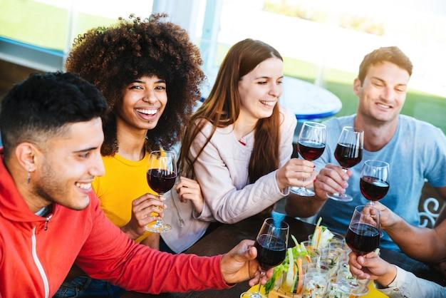 바 레스토랑에서 와인을 마시는 것을 축하하는 다양한 젊은이들