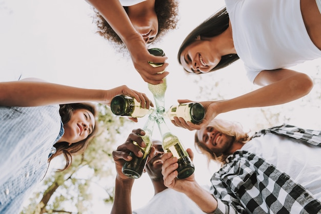 Diverse young people toast with beer bottles.