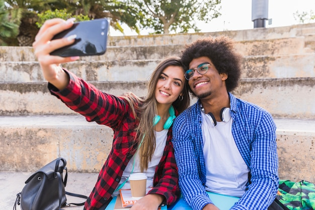 Diverse young student couple sitting on staircase taking selfie on smartphone