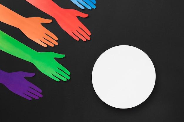 白い円で異なる色の紙の手の多様性の品揃え