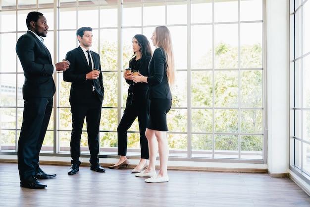 スーツのスタンドアップミーティングに身を包んだビジネスマンの多様性グループ。