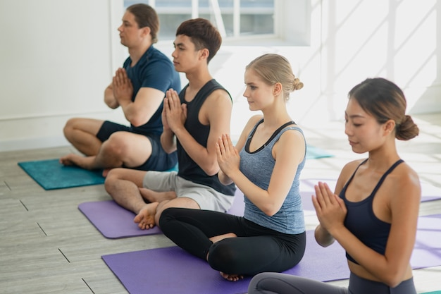 Diversity group of people and friend stretch for exercise yoga and training meditating together