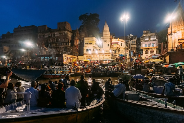Diversity of people in many boats are watching varanasi ganga aarti at holy dasaswamedh ghat.