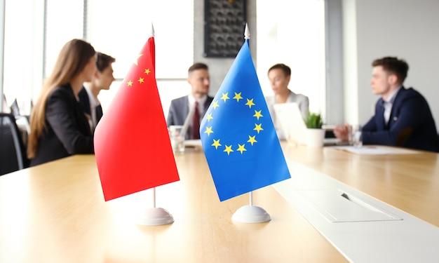 多様性の人々が国際会議のパートナーシップについて話します。中国の旗と欧州連合の旗。