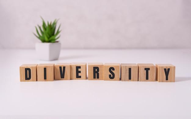 Слово разнообразия в деревянном кубе на белом фоне.