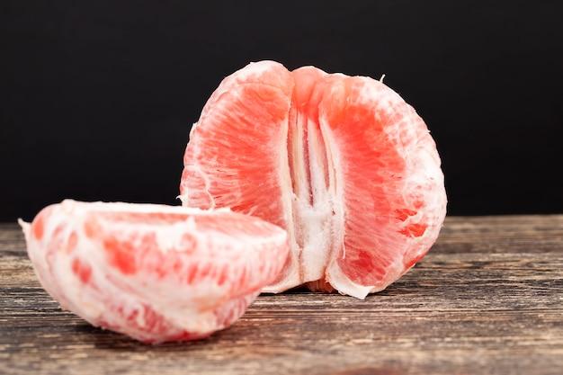 전체 조각으로 나누어 맛있는 새콤한 붉은 자몽 테이블에, 붉은 감귤류 과일, 맛있는 자몽