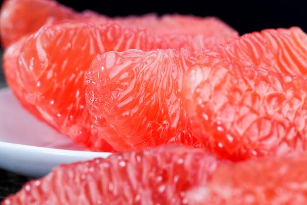 전체 조각으로 나누어 맛있는 새콤한 붉은 자몽 테이블에