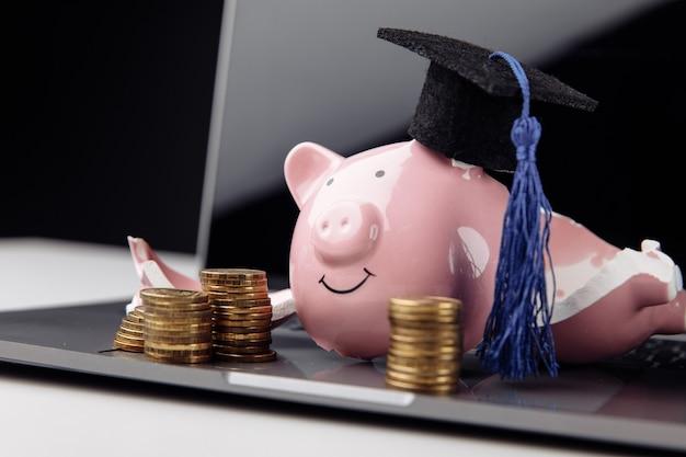 Разделенная копилка в кепке на ноутбуке. экономия на образовании концепции.